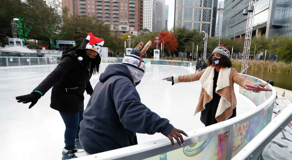 Joy Sewing shows a child from the Houston Southside Community Center how to skate during the 5th annual Year of Joy Holiday Ice Skating Party at Discovery Green.Monday, December 14, 2020, in Houston.