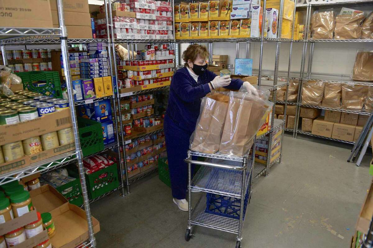 Volunteer Elaine Thorn, of Danbury, pack bags with non-perishable food items to be distributed at the Daily Bread Food Pantry for Thanksgiving, Tuesday morning, November 24, 2020, in Danbury, Conn.