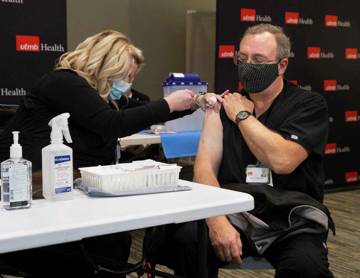 UTMB Galveston Registered Nurse Roy Christian is the first person on the campus to receive a dose of the Pfizer Covid-19 vaccination Tuesday, Dec. 15, 2020, in Galveston. Registered Nurse Michelle Garza performed the vaccination.