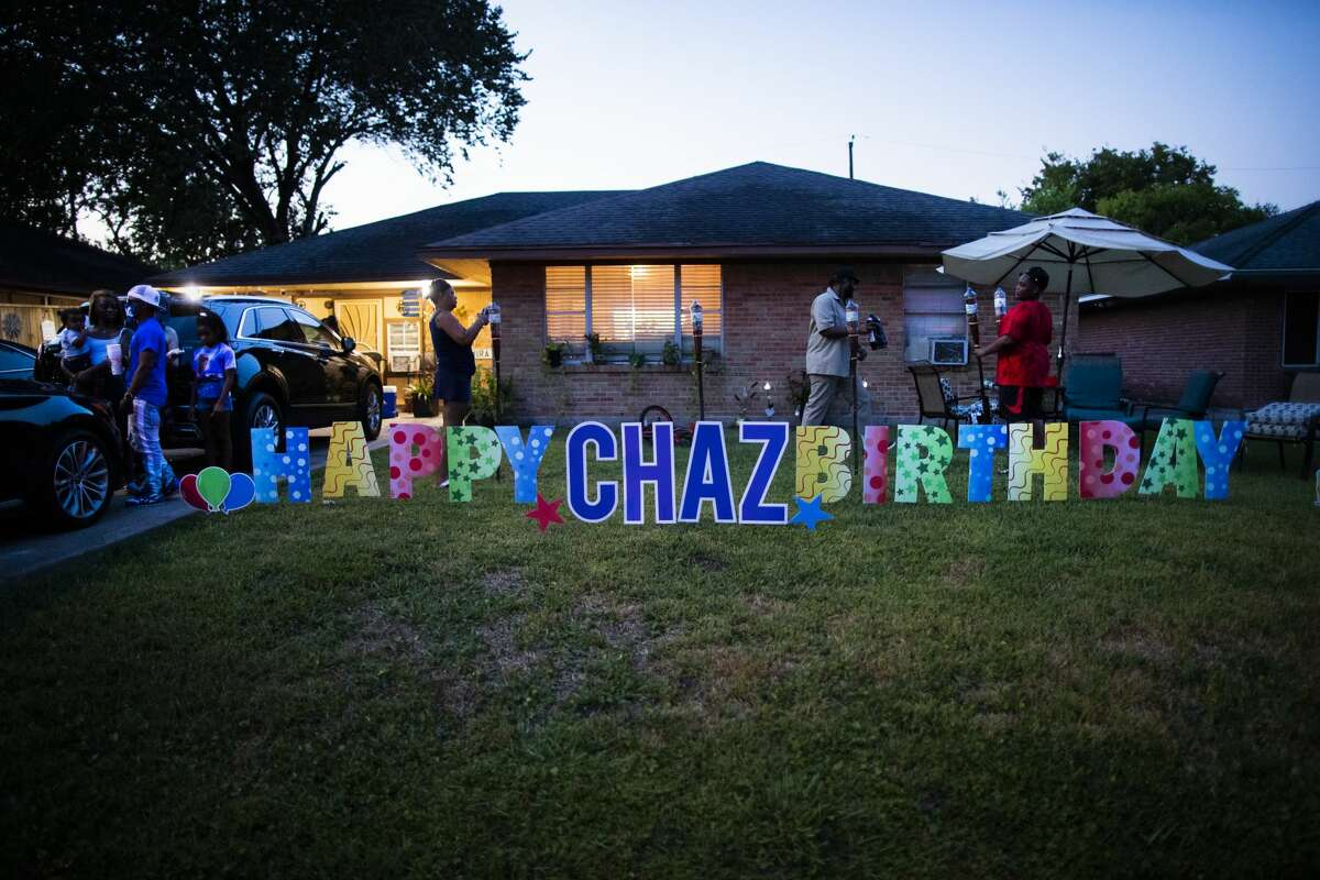 Daphne Nelson and her family members light up tiki torches in front of her home ahead of her son's posthumous birthday party on Aug. 21, 2020, in Houston.