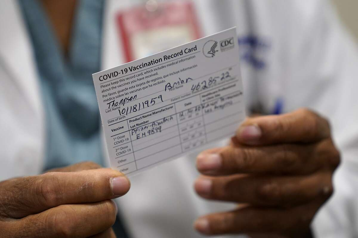 A Kaiser Permanente doctor holds up his vaccination card after getting the Pfizer vaccine Monday, Dec. 14, 2020.