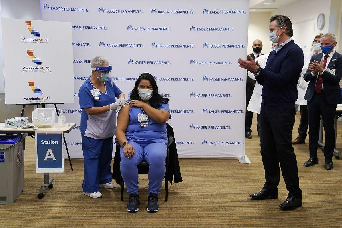 California Gov. Gavin Newsom looks on, far right, as ICU nurse Helen Cordova receives the Pfizer-BioNTech COVID-19 vaccine at Kaiser Permanente Los Angeles Medical Center in Los Angeles, Monday, Dec. 14, 2020. (AP Photo/Jae C. Hong)