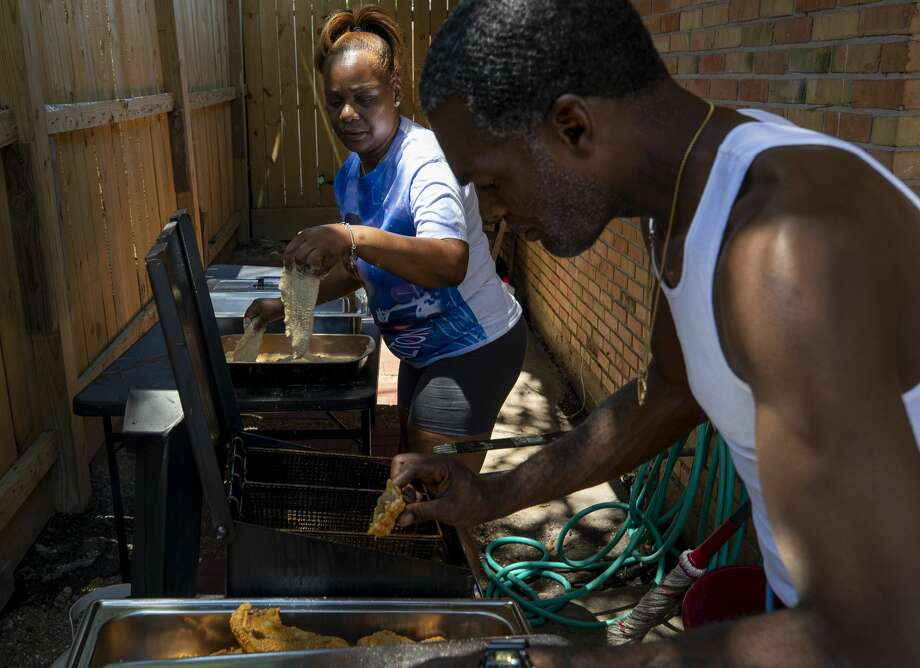 Daphne Nelson, center, and her brother fry catfish fillets during a family get-together at her house June 13, 2020, in Houston. Photo: Godofredo A. Vásquez/Staff Photographer / © 2020 Houston Chronicle