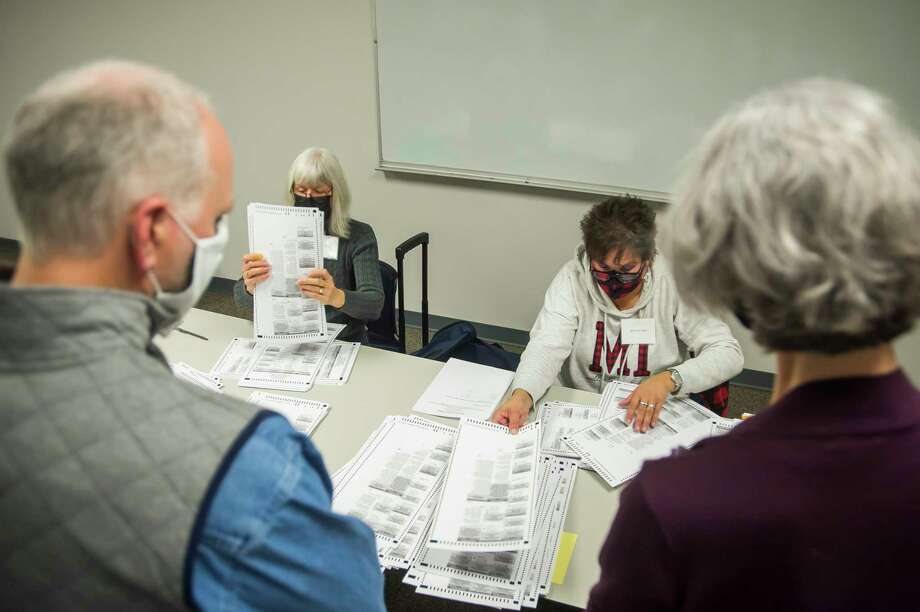 Retired Edenville Township Clerk Lydia Draves, center left, and Warren Township Clerk Linda Anthony, center right, work to count ballots while election watchers stand closeby during an official recount for the race between Midland City Council Ward 1 candidates, incumbent Pam Hall and Jeremy Rodgers, Tuesday afternoon at the Homer Township Fire Department. For more photos, visit www.ourmidland.com. (Katy Kildee/kkildee@mdn.net)