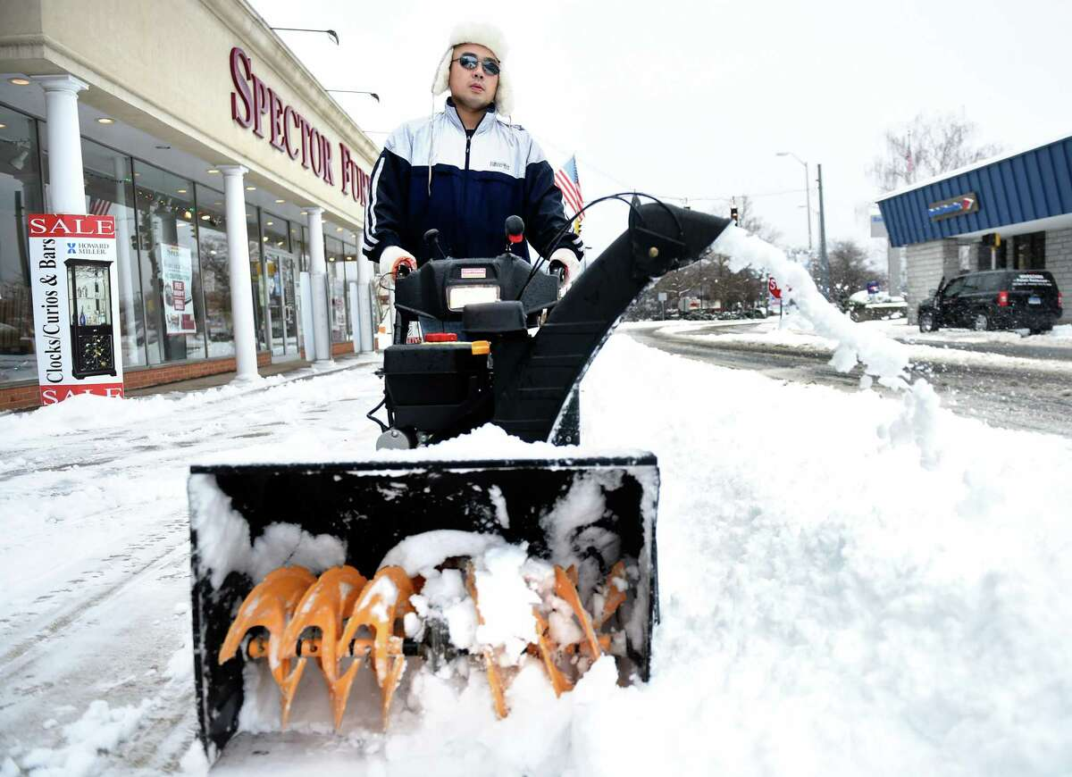 (Arnold Gold-New Haven Register) Tony Dong clears the sidewalk in front of his restaurant, Koi Sushi & Asian Fusion, on Main St. in Ansonia on 12/17/2016.