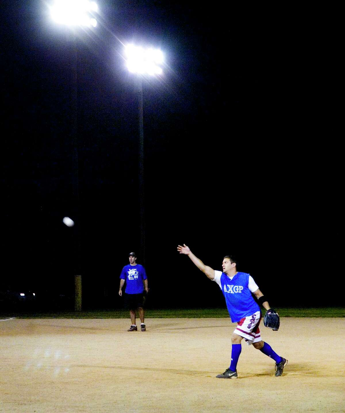 A pitcher throws to the plate during a league softball game at Scalzi Park.