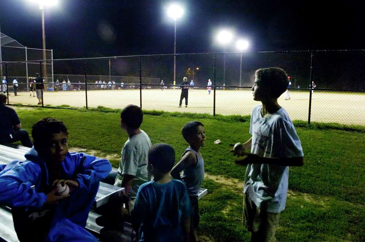 A group of softball fans watch a game one evening at Scalzi Park.