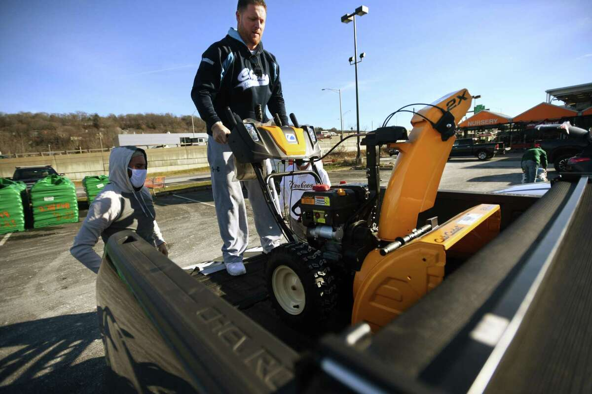 In preparation for Wednesday's impending snow, E.J. Henderson, of Beacon Falls, loads a new snowblower in to his pickup truck with the help of his neighbor Marty Hubbard, left, and his father Ed Henderson, at The Home Depot in Derby on Tuesday.