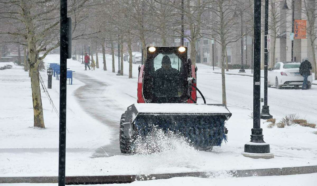A worker clears snow from the walkways surrounding Harbor Points Common Park last February. With heavy snowfall predicted for Wednesday, Mayor David Martin declared a snow emergency.