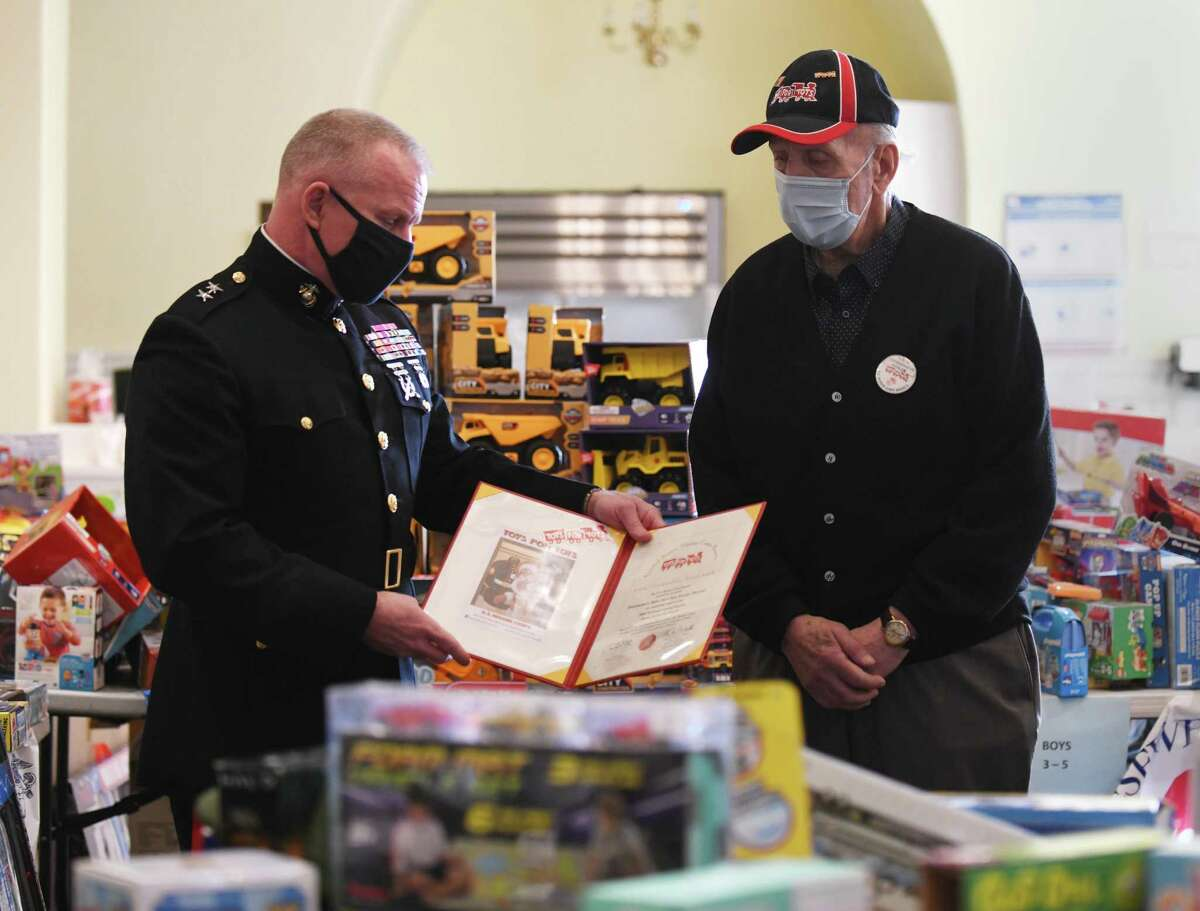 Deputy Commander of the U.S. Marine Corps Reserve Major General Michael S. Martin, left, presents Stamford Toys for Tots Coordinator George Ducanic with a certificate at the Toys for Tots headquarters at St. Mary Church in Stamford, Conn. Tuesday, Dec. 15, 2020. Major General Michael S. Martin, the Deputy Commander of the U.S. Marine Corps Reserve, stopped by Tuesday to thank Ducanic and present him with a certificate for nearly three decades at Toys for Tots.