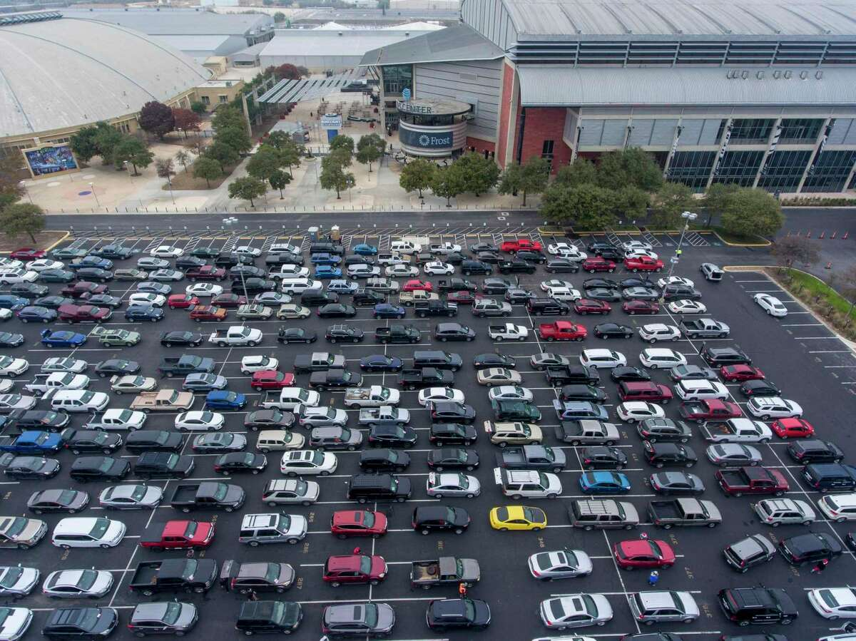 Vehicle wait Tuesday, Dec. 15, 2020 in the AT&T Center parking lot for a San Antonio Food Bank mega food distribution event.