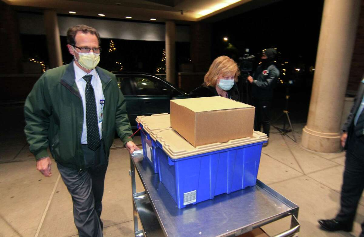 James Duffy, Manager of Pharmacy Operations and Teresa Papsteinm, Director of Pharmacy at Greenwich and Bridgeport Hospitals, wheel in the first shipment of COVID-19 vaccine delivered from Yale New Haven Hospital at Greenwich Hospital in Greenwich, Conn., on Tuesday Dec. 15, 2020.