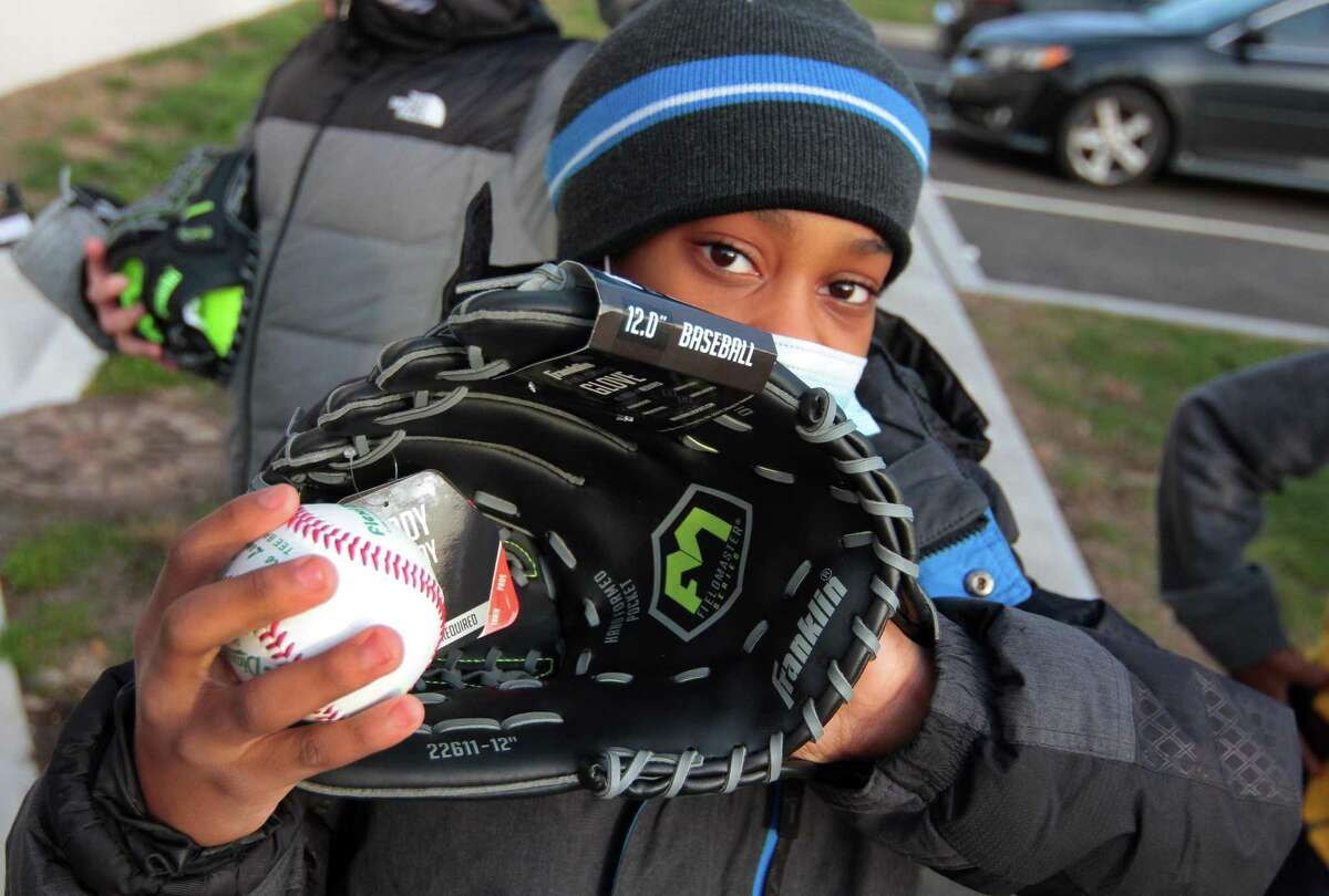 Malachi Johnson, 11, shows off his new baseball and glove he got during the Westhill High School baseball team's ball and glove drive held at the Boys and Girls Club in Stamford on Tuesday.