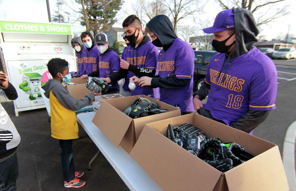 Tyvochee Candido, 11, gets a new baseball and glove at the Westhill High School baseball team's ball and glove drive held at the Boys and Girls Club in Stamford on Tuesday.
