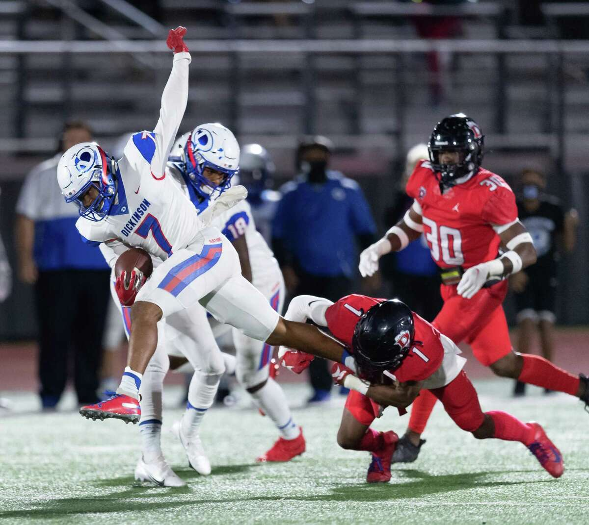 Waylon Presley (7) of the Dickinson Gators is brought down after a short gain in the first half by Blake Smith (1) of the Dawson Eagles during a High School bi-district playoff football game on Thursday, December 10, 2020 at Pearland ISD Stadium in Pearland, Texas.