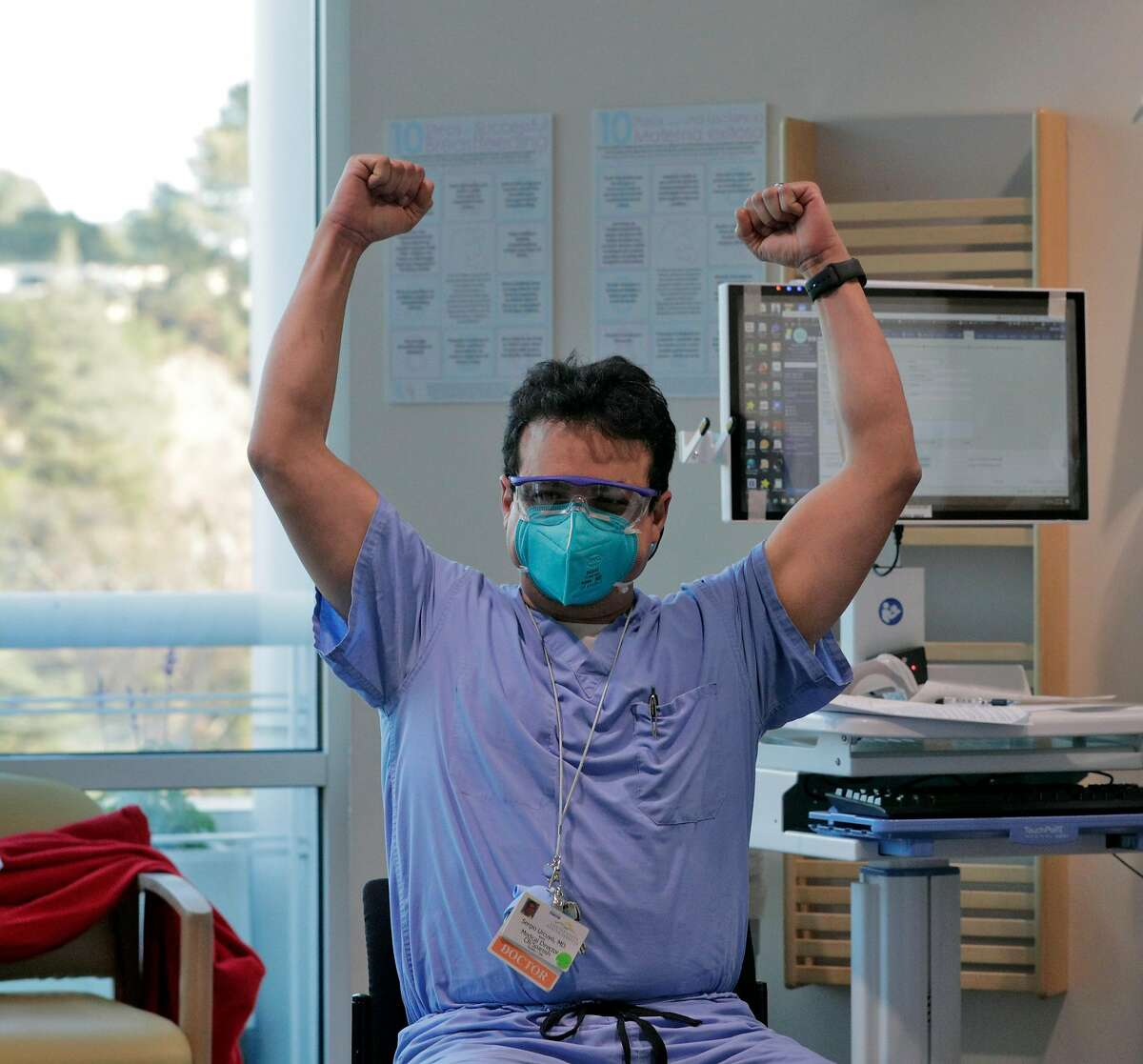 Dr. Sergio Urcuyo raises his arms in triumph after he received his COVID-19 vaccine injection from nurse Kathy Ferris at Contra Costa County Regional Medical Center in Martinez.