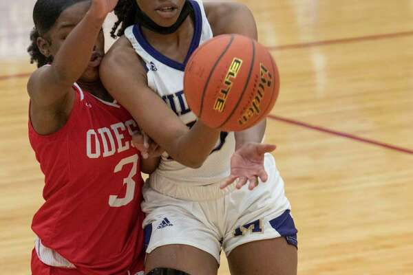 Midland High's Sam Braudaway tries to split Odessa High's Nesha Stephens, 3, and Paige Byford to drive the lane 12/15/2020 at the Odessa High gym. Tim Fischer/Reporter-Telegram