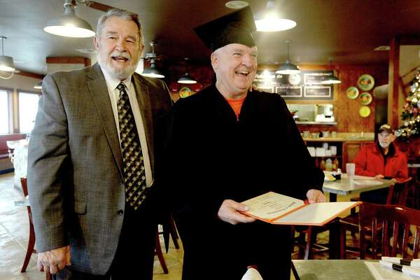 Kent Shaffer officially receives his class of 1974 French High Shool diploma from his then principal Jim Boone at Elijah's Cafe in Woodville Tuesday. Photo taken Tuesday, December 15, 2020 Kim Brent/The Enterprise