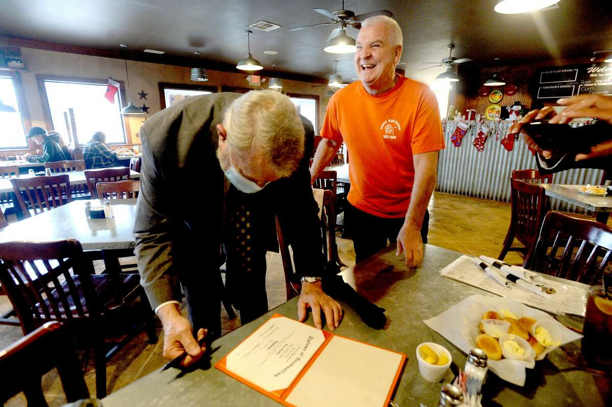 Kent Shaffer stands by as his 1974 principal Jim Boone signs his diploma for an official commencement ceremony at Elijah's Cafe in Woodville Tuesday. Photo taken Tuesday, December 15, 2020 Kim Brent/The Enterprise