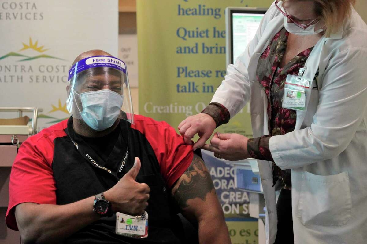 Henri Keeling gives a thumbs up after he recieved his vaccination from Holly Longmuir as medical personnel received the COVID-19 vaccine at Contra Costa County Regional Medical Center in Martinez, Calif., on Tuesday, December 15, 2020.