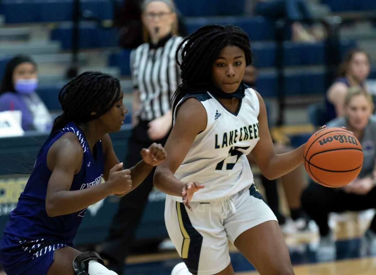 Lake Creek point guard Taliyah Mcshan (15) drives the ball while under pressure from Dayton point guard Jerrica Keener (14) during the third quarter of a non-district girls basketball game at Lake Creek High School, Tuesday, Dec. 15, 2020, in Montgomery.