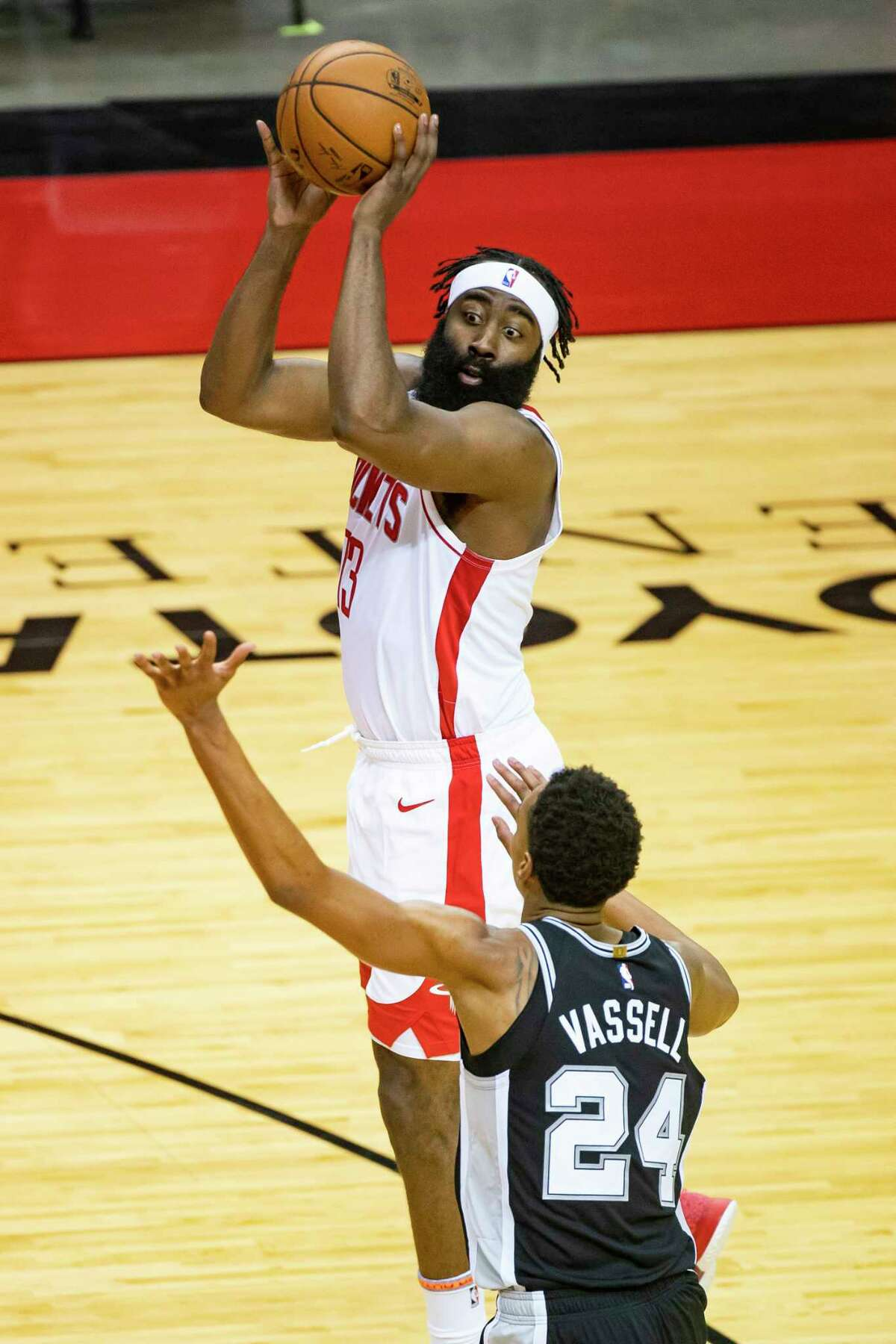Houston Rockets guard James Harden (13) passes over San Antonio Spurs guard Devin Vassell (24) during the first half of a preseason game between the Houston Rockets and San Antonio Spurs on Tuesday, Dec. 15, 2020, at Toyota Center in Houston.