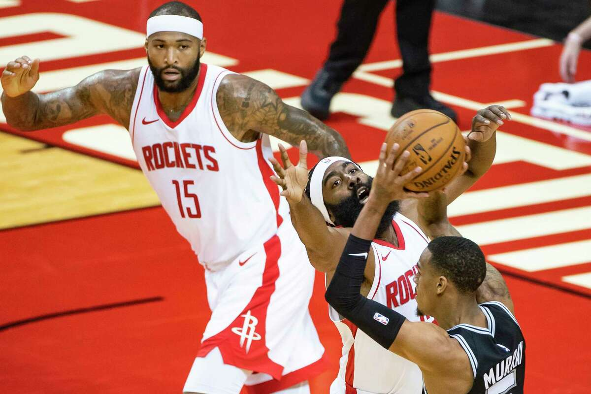 James Harden contests a pass from Spurs guard Dejounte Murray during the first half of Tuesday's preseason game at Toyota Center.