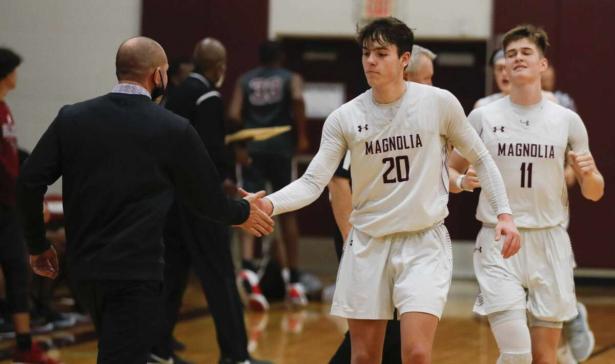 Magnolia guard Mason Machado (20) gets a high-five from head coach Derek Cain after making three straight freethrows with 1.43 seconds remaining to give the Bulldogs a 54-51 win over Waller during a high school basketball game at Magnolia High School, Tuesday, Dec. 15, 2020, in Magnolia.
