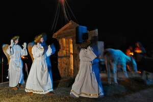 Angels converge on the manger with Jesus, Mary and Joseph inside, during the live nativity performed by the youth group from the Bethlehem Lutheran Church on Sunday evening Dec. 18, 2011, in Delmar, N.Y. The church youth group has performed the live nativity for over 30 years. (Philip Kamrass / Times Union )