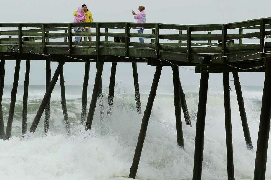 KILL DEVIL HILLS, NC - SEPTEMBER 03: People stand on the Avalon Fishing Pier as heavy surf comes in, on September 3, 2010 in Kill Devil Hills, North Carolina. Hurricane Earl caused heavy surf as it passed the Outer Banks early Friday morning causing minimal damage.  (Photo by Mark Wilson/Getty Images) Photo: Mark Wilson, Getty Images / 2010 Getty Images