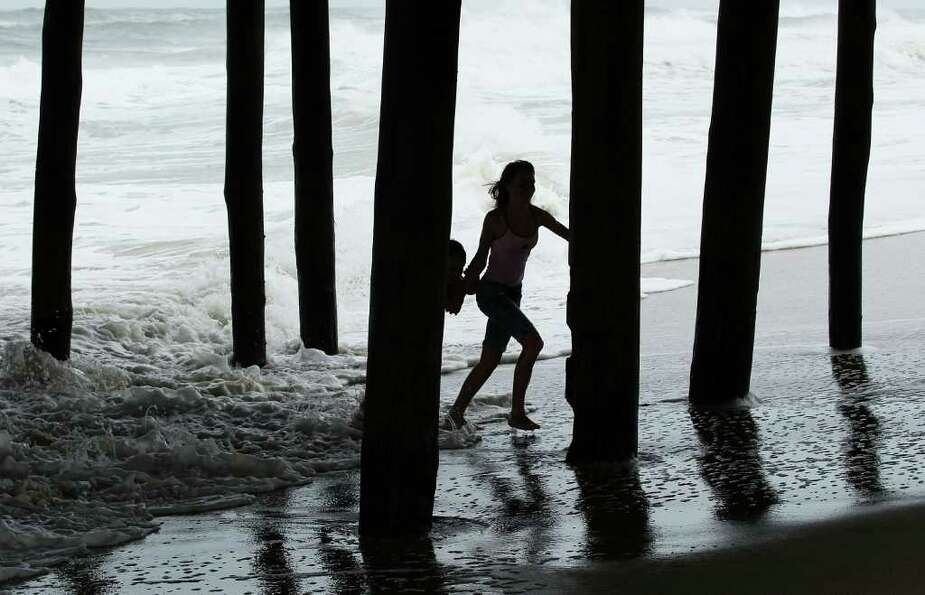 KILL DEVIL HILLS, NC - SEPTEMBER 03:  Two young girls play in the surf underneath the Avalon Fishing