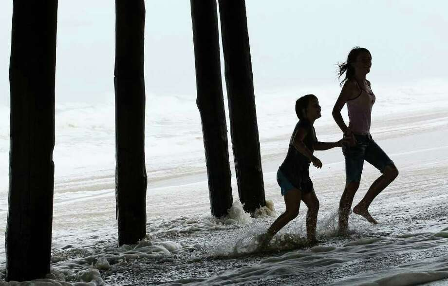 KILL DEVIL HILLS, NC - SEPTEMBER 03: Two young girls play in the surf underneath the Avalon Fishing Pier, on September 3, 2010 in Kill Devil Hills, North Carolina. Hurricane Earl caused heavy surf as it passed the Outer Banks early Friday morning causing minimal damage.  (Photo by Mark Wilson/Getty Images) Photo: Mark Wilson, Getty Images / 2010 Getty Images