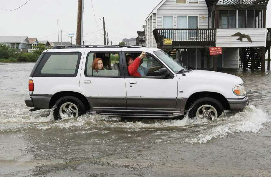 KILL DEVIL HILLS, NC -SEPTEMBER 03: A car drives on a flooded beach road on September 3, 2010 in Kill Devil Hills, North Carolina. Hurricane Earl was downgraded to a category 2 before brushing the Outer Banks early Friday morning causing minimal damage.  (Photo by Mark Wilson/Getty Images) Photo: Mark Wilson, Getty Images / 2010 Getty Images