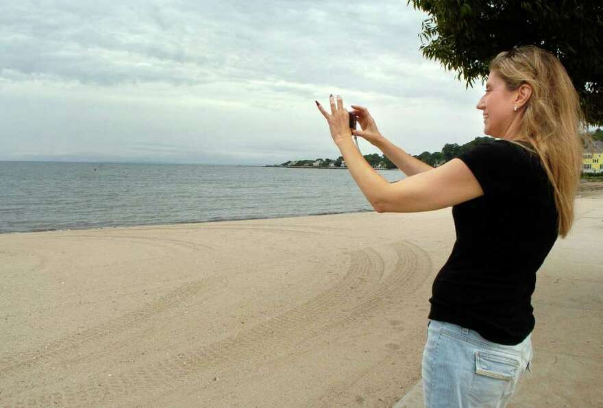 Robin Duvall takes a photo of the darkening sky on West Beach in Stamford, Conn. on Friday September