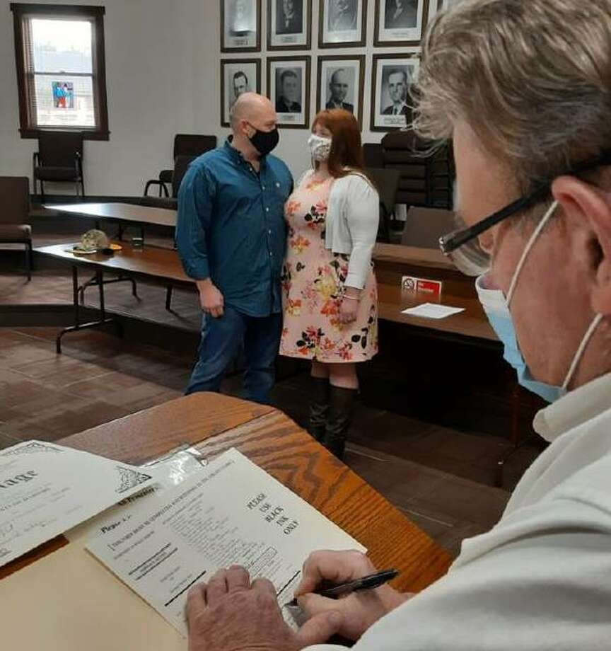 Highland Mayor Joseph Michaelis, left, signs the marriage license for Joseph and Kimberly Laxson Friday, Dec. 11, in Highland City Hall. Because COVID-19 restricted a wedding in the Madison County Courthouse and travel to Alaska for a family ceremony, the couple were wed by Michaelis. Photo: Submitted