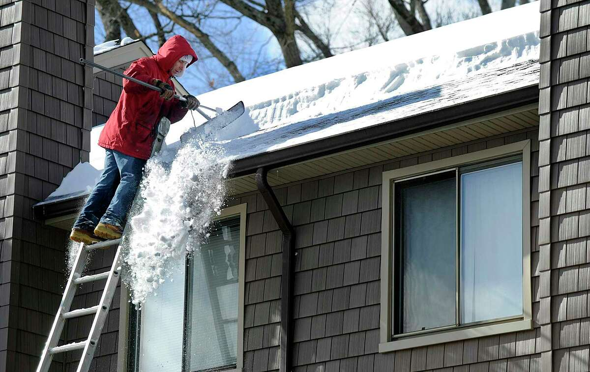 An employee of Scalzo Property Management rakes snow off the roof of buildings at Shepherd Hill Condominiums in Danbury Friday morning, Feb. 10, 2017.