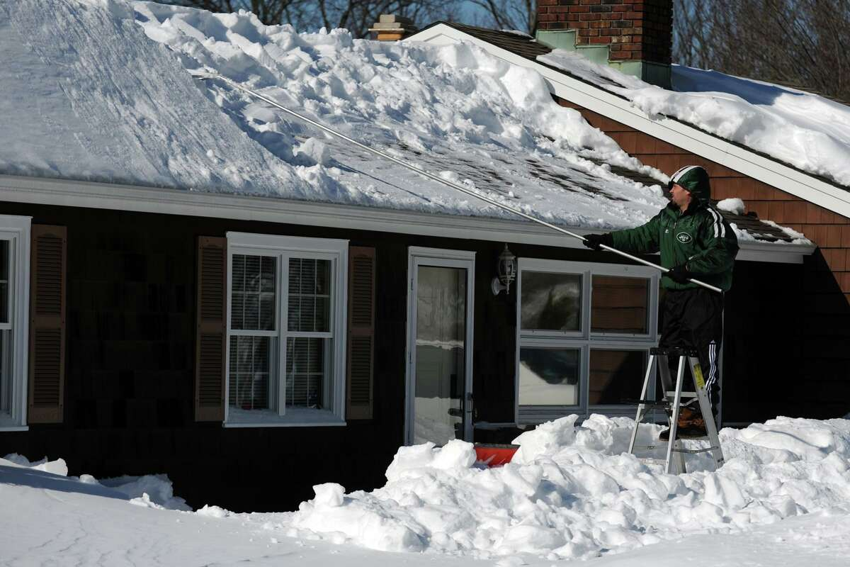Joe Monte uses a roof rake as he works to works to remove a large snow drift from the roof of his home on Eurika Ave., in Stratford, Conn., Feb. 10, 2013.