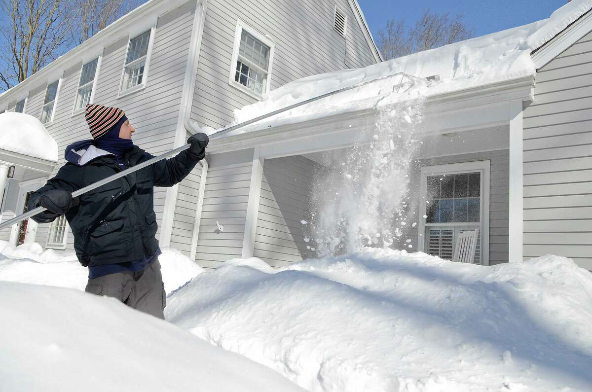 T.R. Coccaro uses a roof rake on his home as he contends with the snow in Southport, CT on Sat., Feb. 9, 2013, following a blizzard that dumped up to three feet of snow across the state.