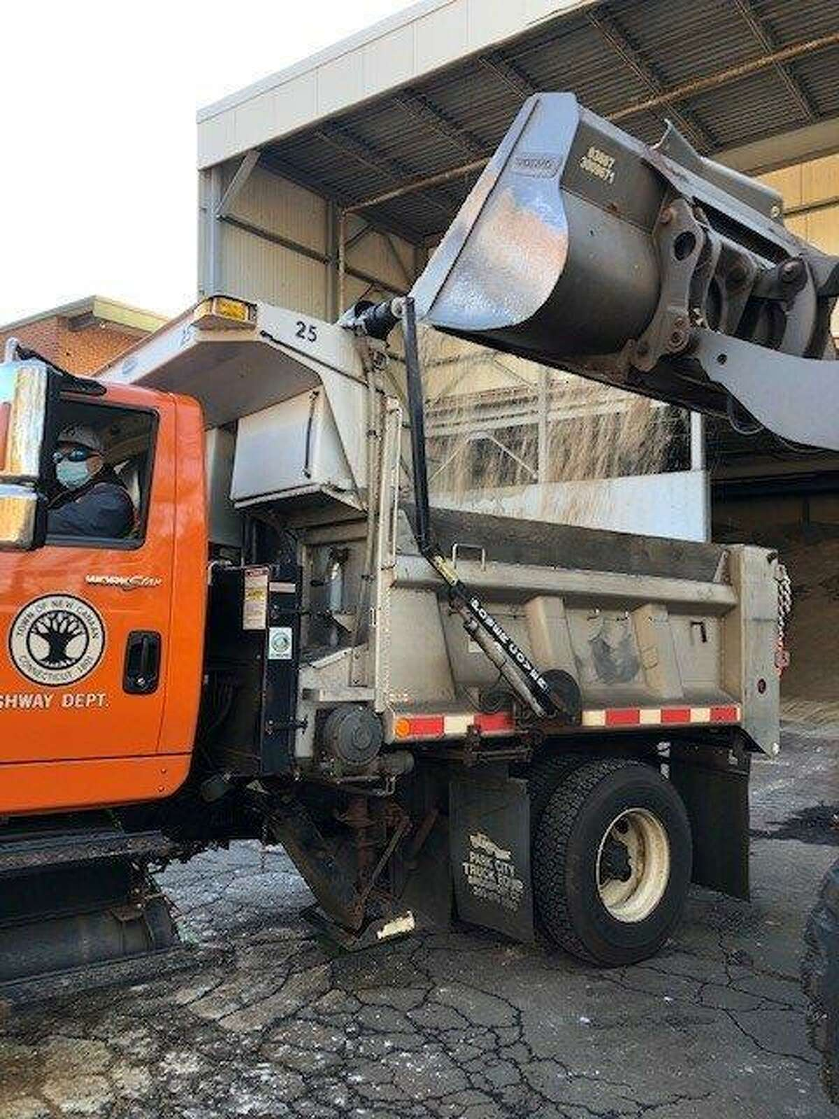 Pete Merduri of the New Canaan Highway Department gets a bucket of treated salt loaded in anticipation of a foot or more of snow expected to start falling Wednesday afternoon.