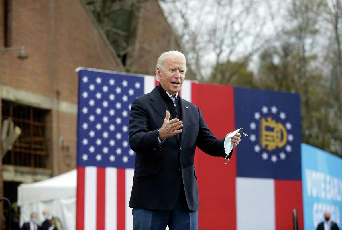 President-elect Joe Biden acknowledges the crowd Tuesday as he attends a rally with Democratic Senate nominees Raphael Warnock and Jon Ossoff in Atlanta.