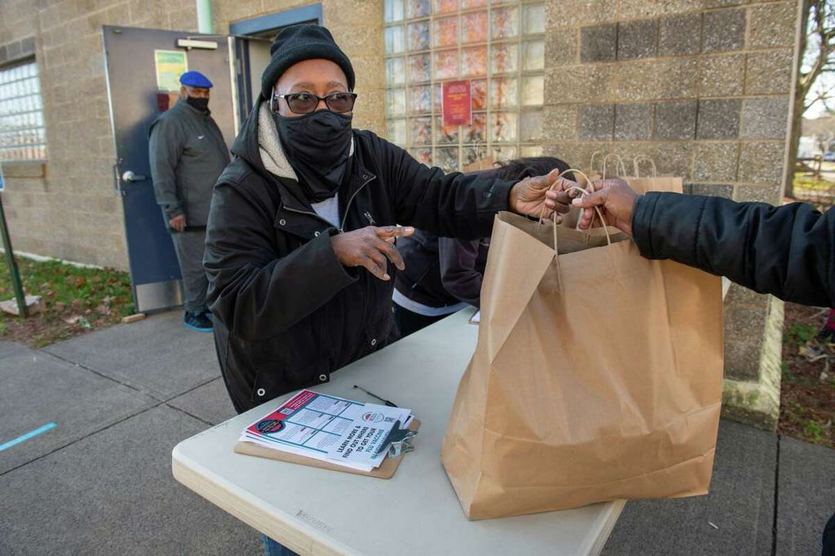 Sharon Stevens, director of Women of the Village Food Pantry, asks a client picking up food at the Dixwell neighborhood food pantry if they have gotten the flu vaccine yet. Stevens is one of several outreach workers helping to encourage New Haven residents to get the vaccine.