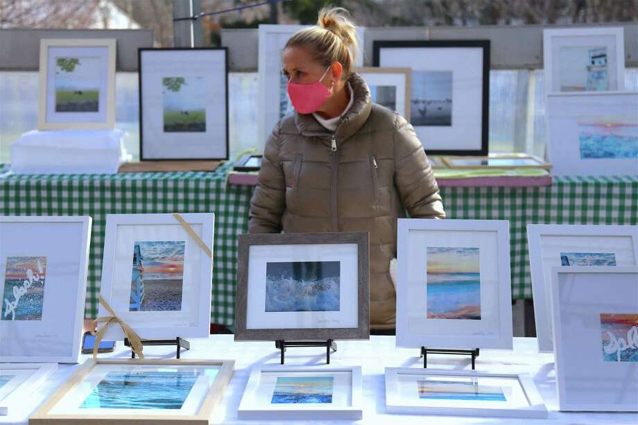 Photographer Jessica Ryan, of Southport, stands by her work at the Westport Farmer's Market on Tuesday, Dec. 15, 2020.
