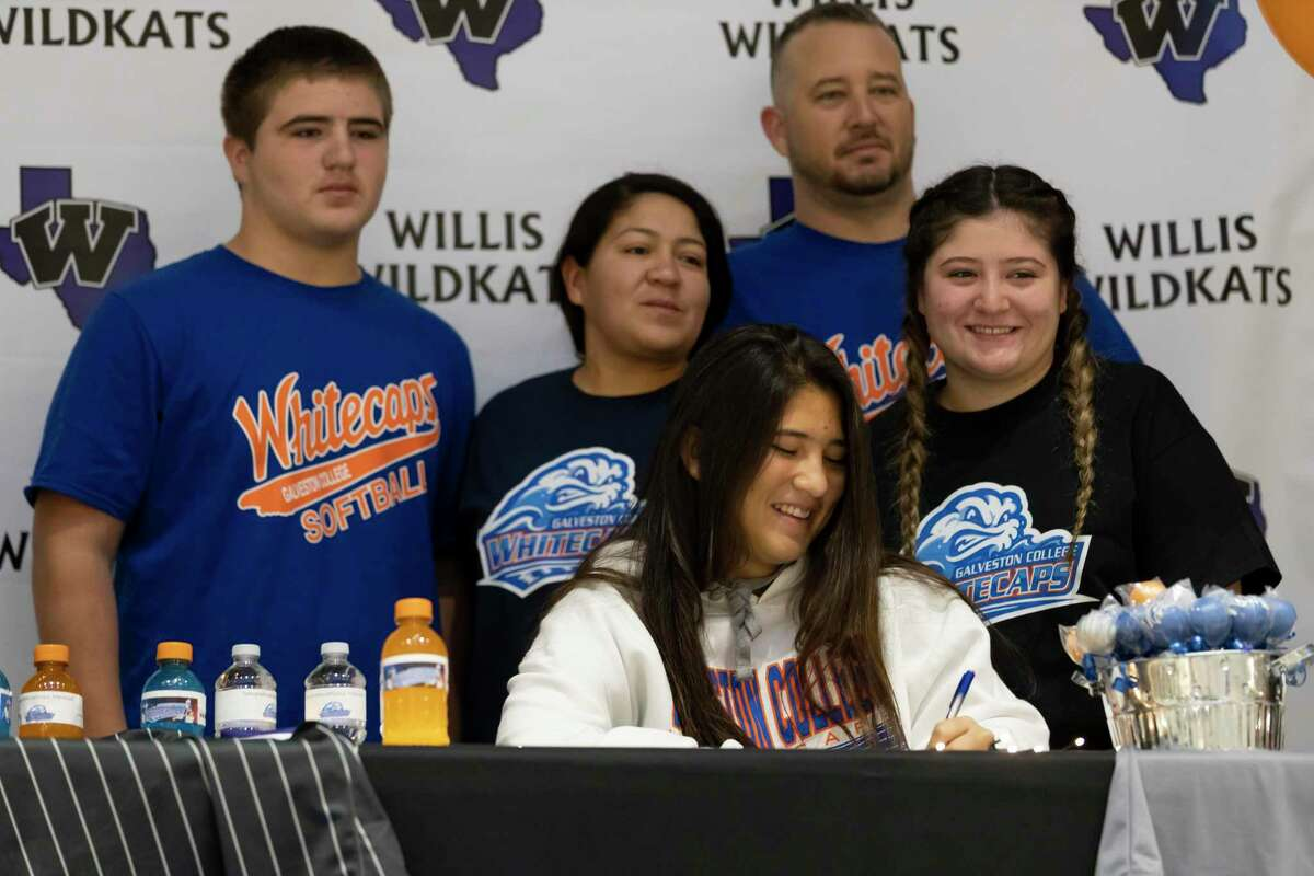 Marissa Fletcher, who signed with Galveston College's softball team, signs alongside her family during a National Signing Day ceremony at Willis High School, Wednesday, Dec. 16, 2020, in Willis.