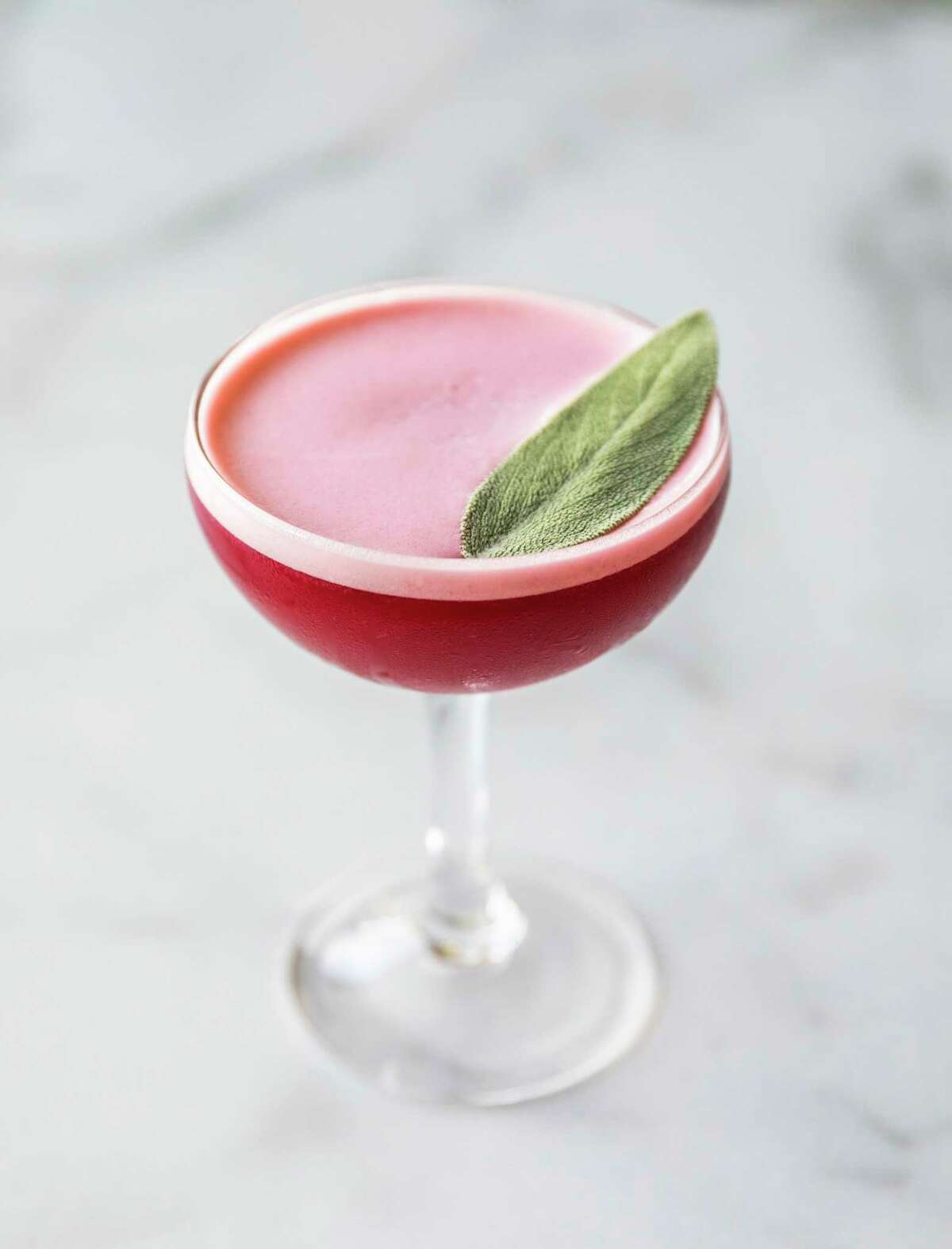 The Tighten Up is a holiday cocktail from Relish Restaurant & Bar made with cognac, Calvados, cranberry syrup and egg white, flavored with sage leaves.