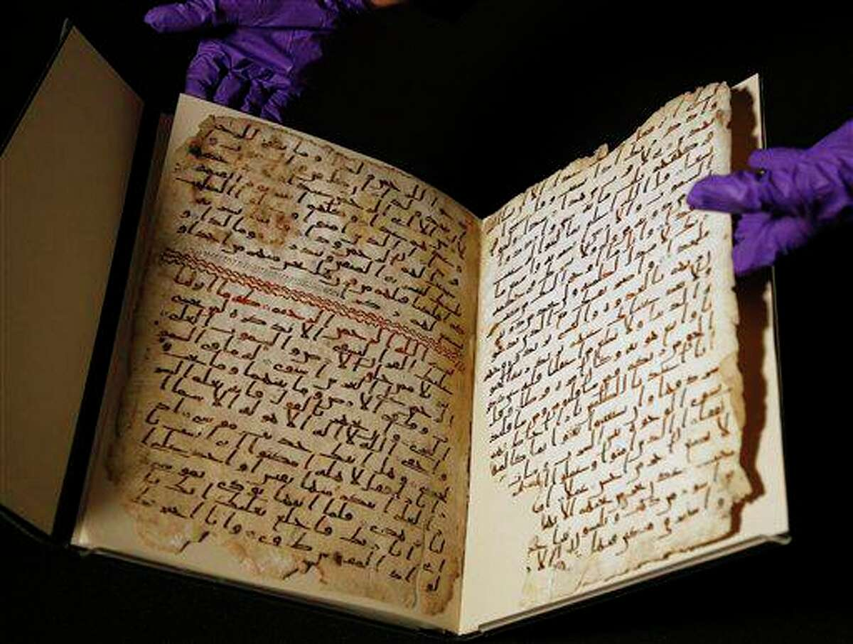 A university assistant shows fragments of an old Quran at the University in Birmingham in 2015.