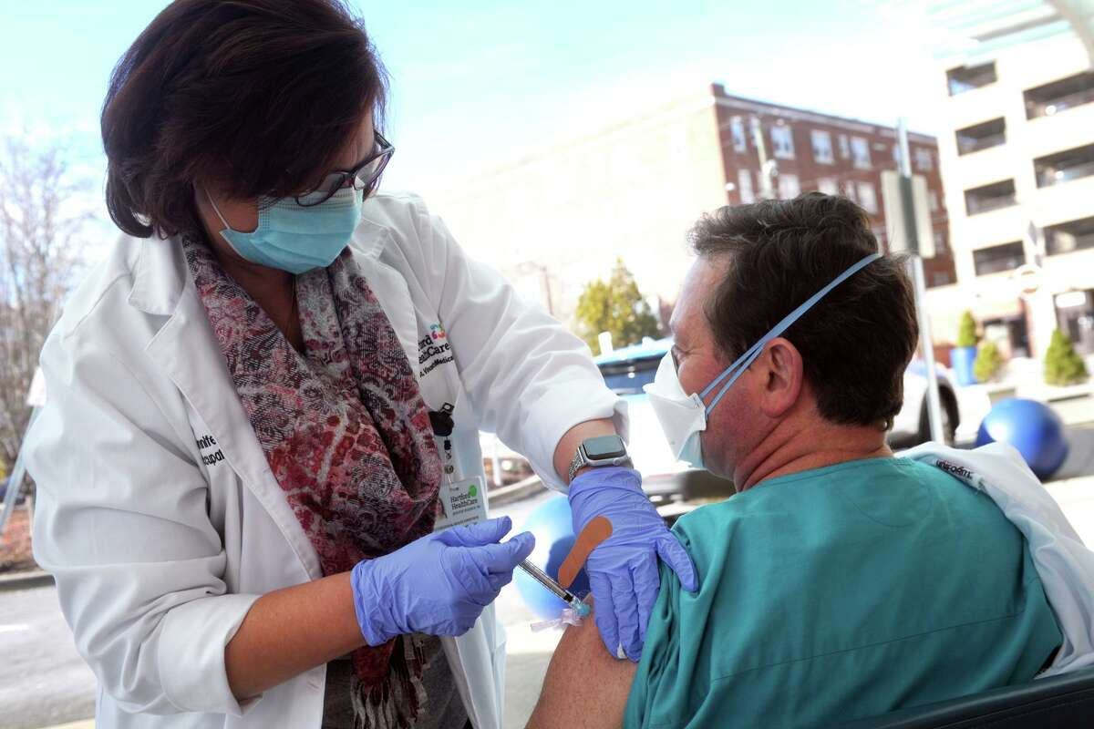Registered nurse Jennifer Woznick administers a dose of the COVID-19 vaccine for Dr. Robert Suriani in front of St. Vincent's Medical Center, in Bridgeport, Conn. Dec. 15, 2020. The hospital received their first shipment of the vaccine Tuesday morning and began administering shots to medical staff in the afternoon.