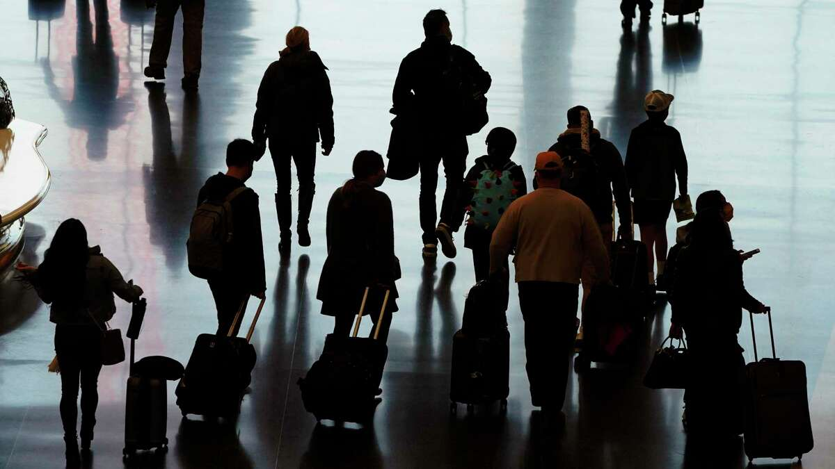 Travelers walk through the Salt Lake City International Airport in Salt Lake City, a day before Thanksgiving.