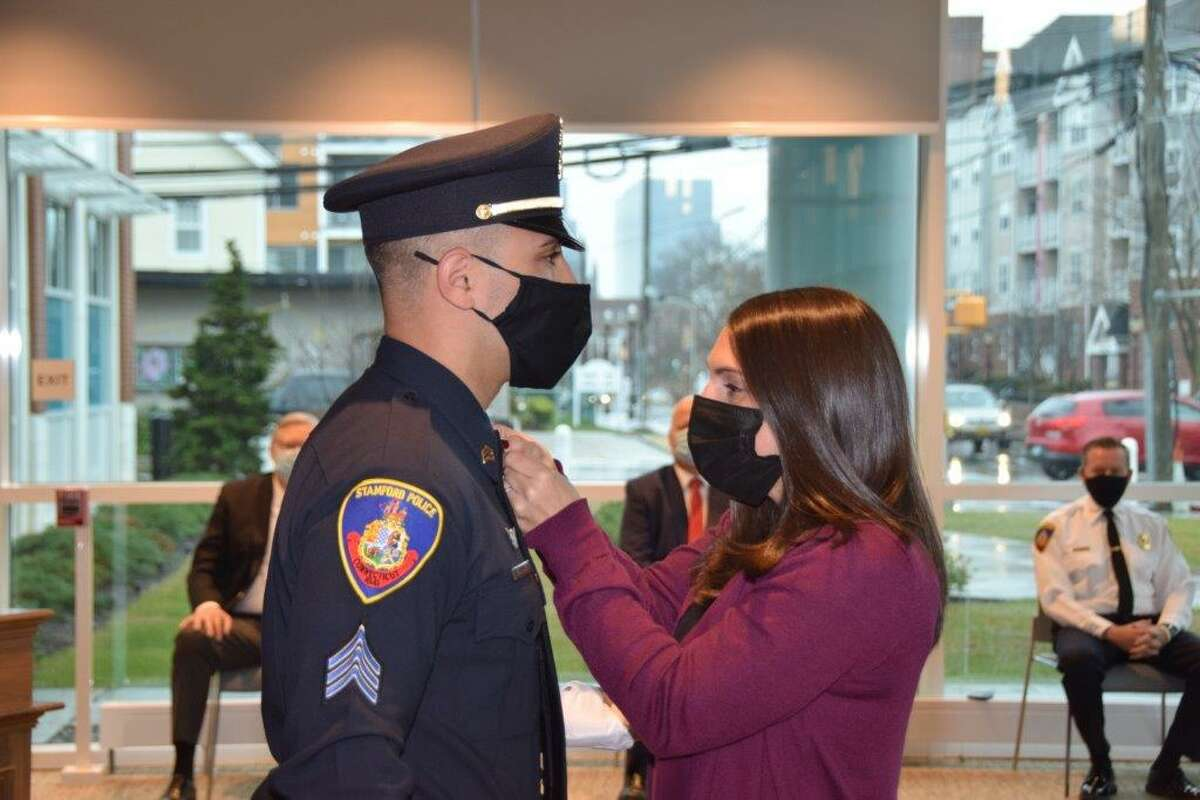 """New Sgt. Christopher Felmen-Merced has his gold chevrons pinned to his collar by his wife Nicole at a promotion ceremony at Stamford police headquarters on Dec. 14, 2020. """"I've always had the affinity to be a police officer. My mom was a teacher in Vietnam, and my dad was a police officer in Vietnam,"""" said Nguyen. """"I've heard the stories of what they have gone through, and I've kind of followed in their footsteps to America."""" When his son Michael Jr., 9, was asked what he wanted to be when he grew up, there was no hesitation - true blue."""