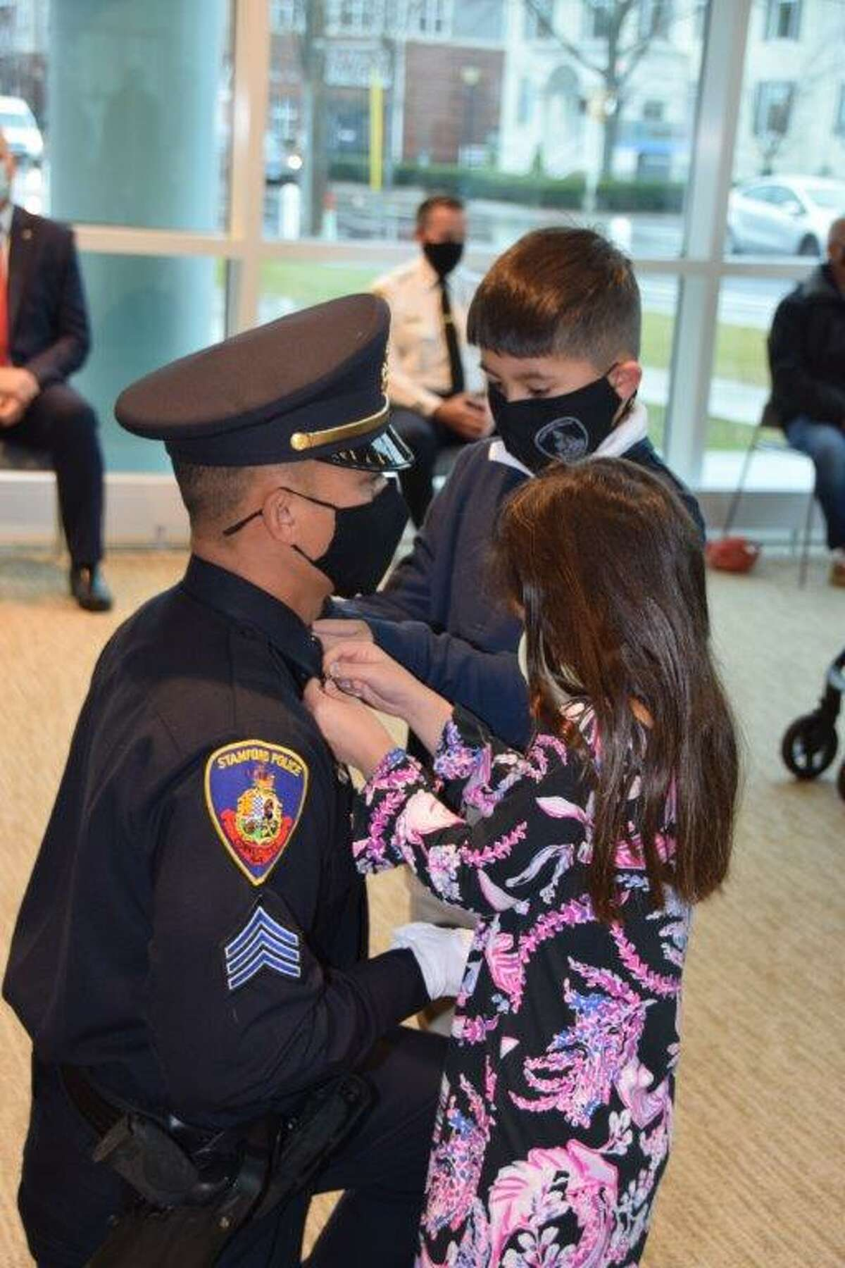 Newly minted Sgt. Michael Nguyen has his gold chevrons pinned to his collar by his son Michael Jr., 9, and daughter Kyla, 7, at a promotion ceremony held at Stamford police headquarters on Dec. 14, 2020. Felman-Merced, 32, a native of Beacon, N.Y., has been in the department for eight years.