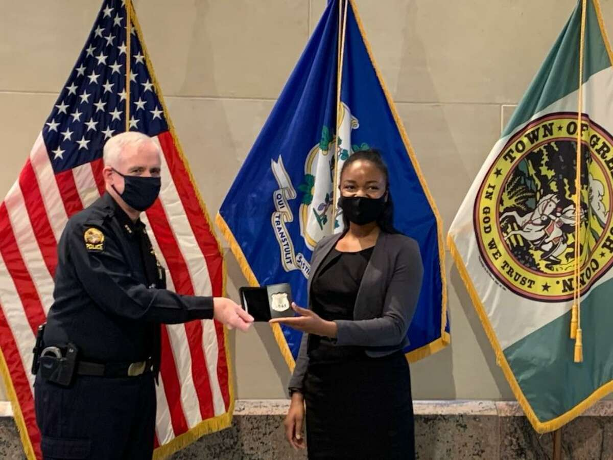 New Greenwich Police Officer Turiya Hamilton is sworn in recently in Greenwich, Conn., and receives her badge.